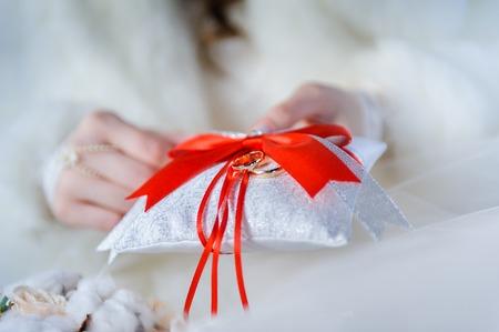 Wedding rings on decorative white pillow