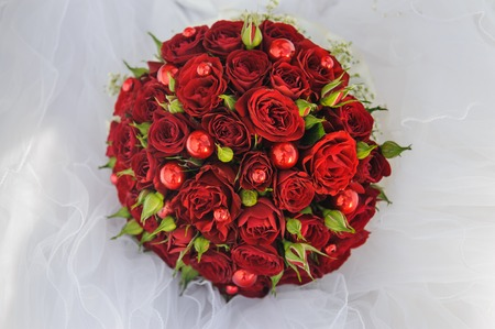 Wedding bunch bouquet of red roses on the veil
