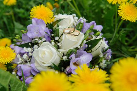 Wedding bouquet and wedding rings in dandelions