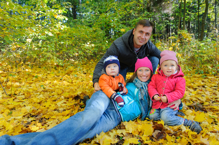 Happy Family of four in autumn park on yellow foliage