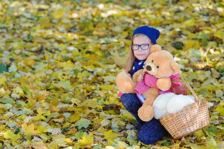 Little girl with Teddy bear in autumn outdoor