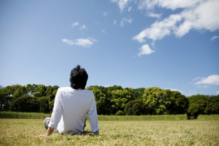 Young man sitting on the grass photo