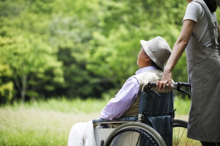 in home care: Anziano in una sedia a rotelle e il suo assistente