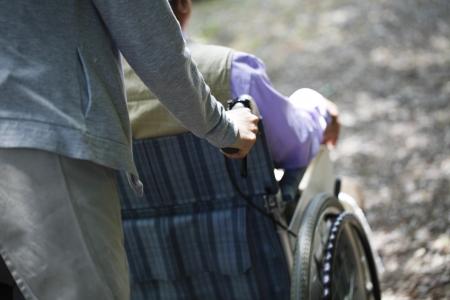 persona en silla de ruedas: Mayor en una silla de ruedas y ayudante