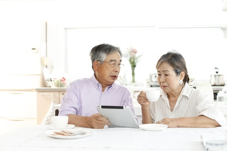 asian wife: Senior tablet View Stock Photo