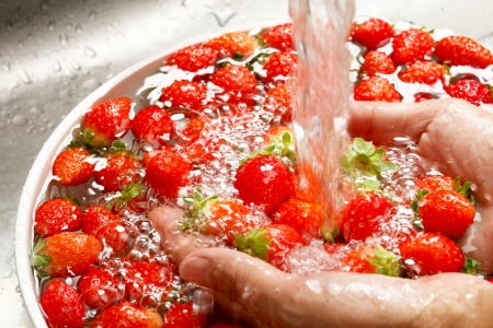 increase fruit: Wash the strawberries Stock Photo