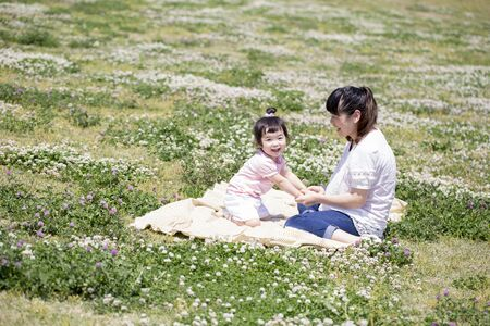 Japanese mother and child picking clover flowers