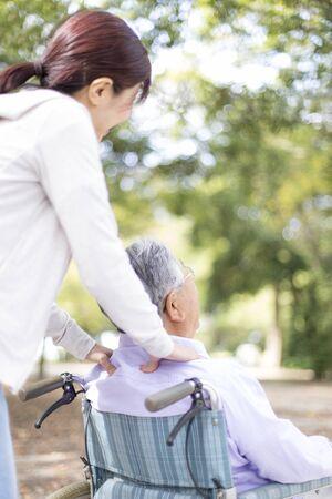 Nursing Care Image, Elderly and Helper in Wheelchair, Walking in the Park