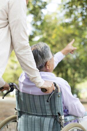 Nursing Care Image, Elderly and Helper in Wheelchair, Walking in the Park Imagens