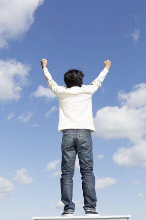 Oriental Young Man Rear View, blue sky background Standard-Bild