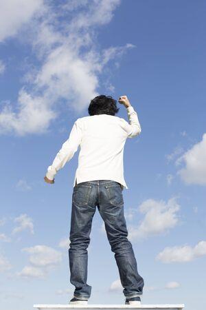 Orientalischer junger Mann Rückansicht, Hintergrund des blauen Himmels
