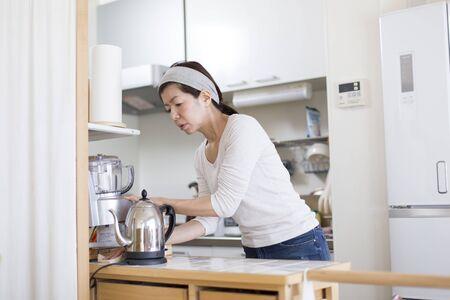 Une femme nettoie la cuisine où elle vit seule Banque d'images