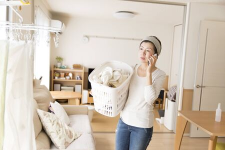 Japanese woman calling while doing housework Stock Photo