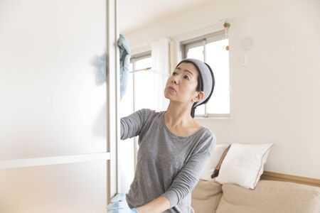 Japanese middle woman cleaning the living window