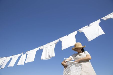 Japanese woman doing laundry on the roof on a sunny day Standard-Bild