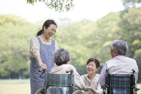 Japanese helper woman caring for wheelchair senior
