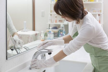 A woman cleaning a sink