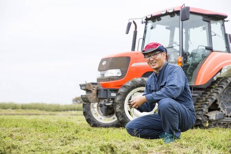 Young Japanese farmer working on a tractor