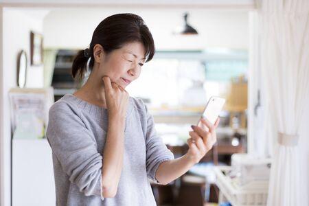 A middle woman watching smartphone 版權商用圖片