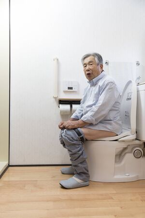 Japanese senior man defecate in the toilet at home