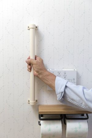Senior man grabbing handrail in toilet at home Archivio Fotografico