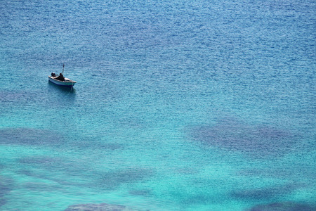 A fishing boat floating in a tropical ocean Stock Photo
