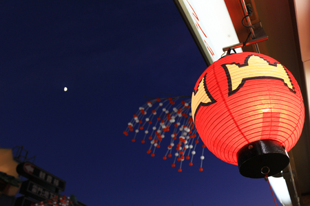 Japanese lanterns decorated in the night shopping street where the moon can be seen