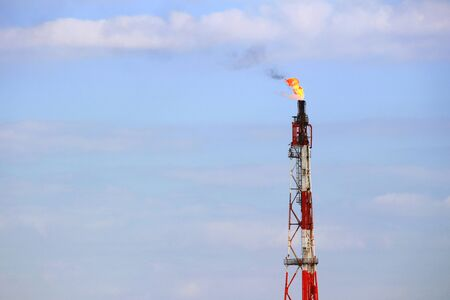 A view of the flame rising from the chimney of an oil complex Stok Fotoğraf