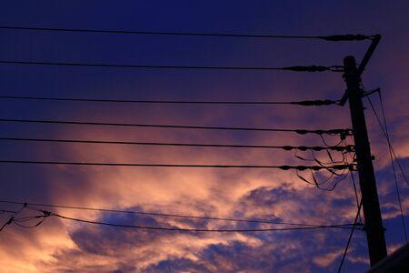 Purple and orange sunset sky and power pole