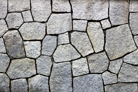 Photo of a wall of white stones stacked as background material