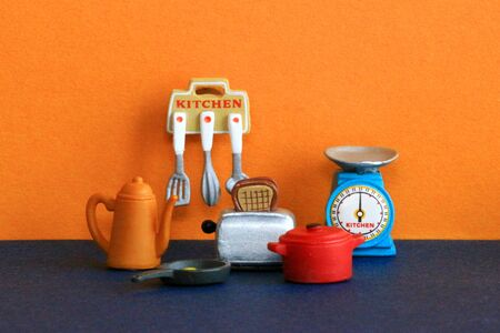 Cookware figures lined up in a colorful kitchen Stockfoto