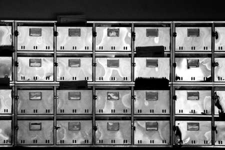 Stainless steel mailboxes lined up at the back entrance of an old multipurpose building in Japan Banque d'images