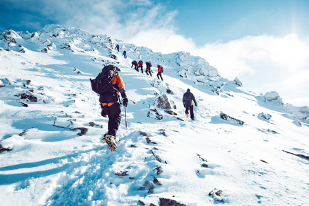 A group of climbers ascending a mountain in winter Stockfoto