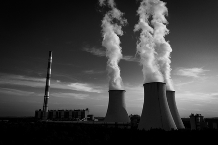 A Power plant with white smoke over its chimneys Standard-Bild - 117005904