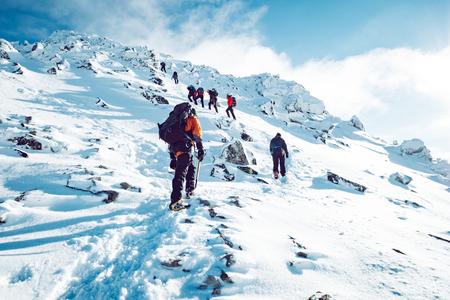 Een groep klimmers die in de winter een berg beklimt