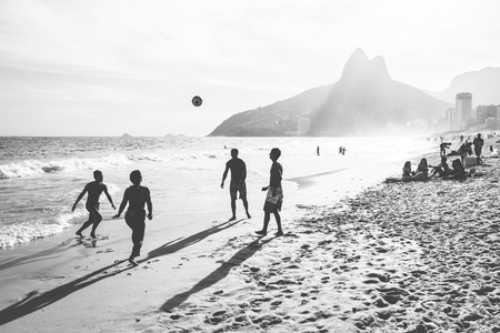 RIO DE JANEIRO, BRAZIL - FEBRUARY 24, 2015: A group of Brazilians playing on the shore of Ipanema Beach, with the famous Dois Irmaos mountain behind them