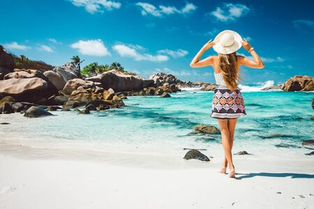 A young girl standing in shallow water on La Digue island, Seychelles
