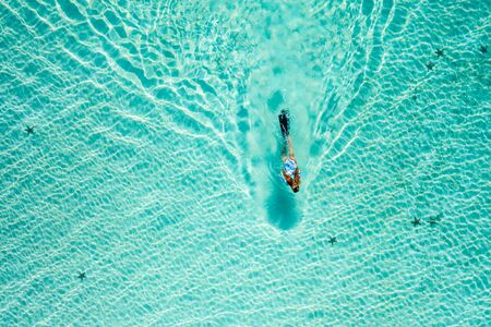 Top down view of a girl swimming in a lagoon. Aerial view of slim woman floating on the water. Summer vacation concept 스톡 콘텐츠