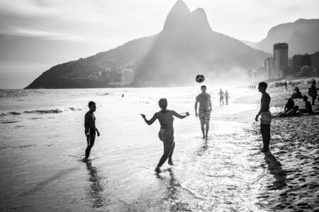 Rio de Janeiro, Brazil- February 24, 2015: A group of Brazilians playing on the shore of Ipanema Beach, with the famous Dois Irmaos mountain behind them