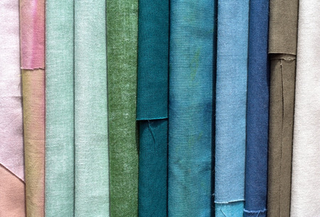 canva: Rolls of textile, cloth and tissue of various colours, background