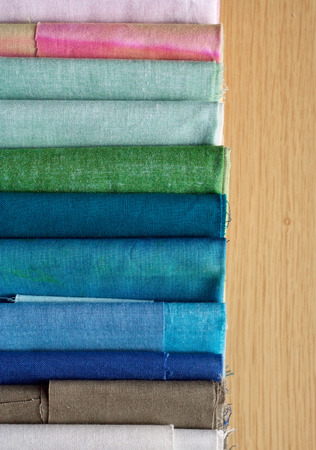 canva: Rolls of textile, cloth and tissue of various colours on wood background