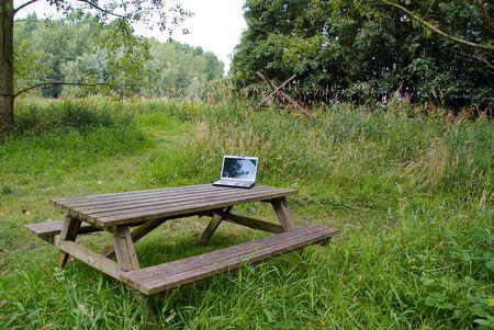 picknick: A black laptop on a picknick table in the field Stock Photo