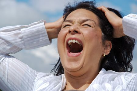 Woman is screaming out loud, hands to her head photo