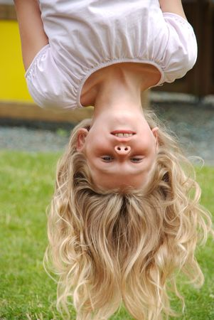 upside down: Cute girl hanging upside down at playground Stock Photo