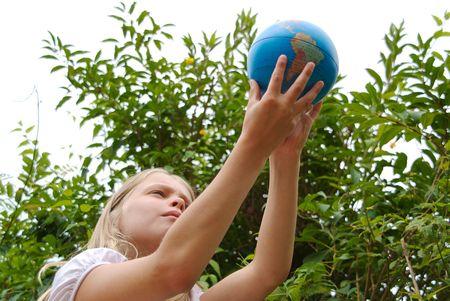 Una joven est� sosteniendo el mundo en sus manos Foto de archivo - 5400369