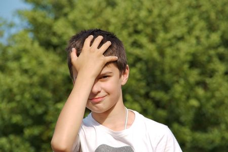 embarassment: A young kid made a mistake, hitting himself on the forehead. Stock Photo