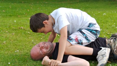 A boy is fighting his father, lying on the grass photo