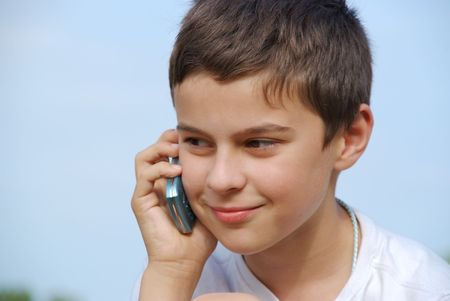 phonecall: A young boy outside is making a phonecall with his cellphone.