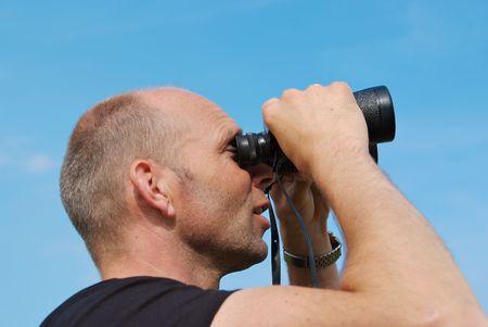 남자가 한 쌍의 쌍안경을보고 오른쪽을보고 있습니다.