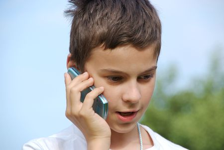 phonecall: A young kid making a phonecall with his cellphone Stock Photo